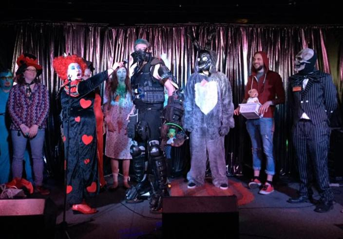 First-place winner Apocalypse Owl speaks with emcee DJ Callisto, while flanked by second-place winner Frank from Donnie Darko and third-place winner Regan from The Exorcist.